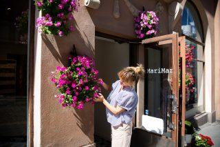 Nainen hoitaa kivijalkaliikkeen kukka-asetelmia.