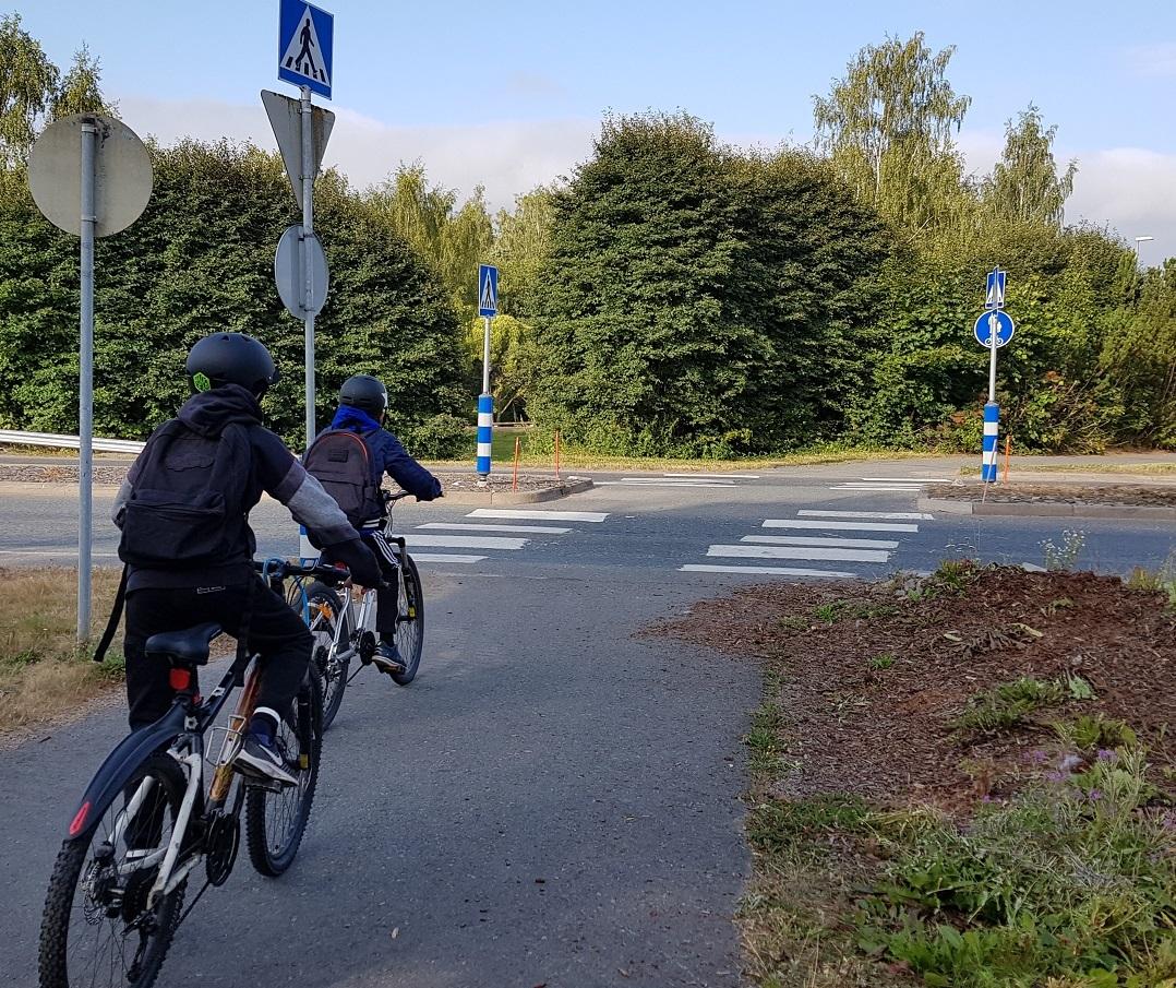 Koululaisia pyöräilemässä kouluun ja suojatien ylitys