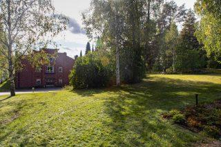Puistomainen alue Hennalan vanhalla kasarmialueella. Taustalla punatiilinen kasarmirakennus.