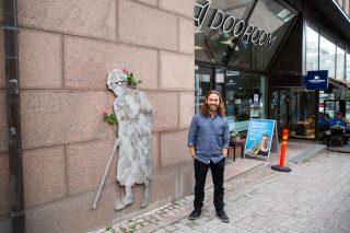 Taiteilija Sami Leutola teoksensa vieressä. Teos on teräksinen mummo, jolla on kävelykeppi.