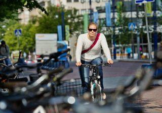 Nainen pyöräilee kaupungilla.