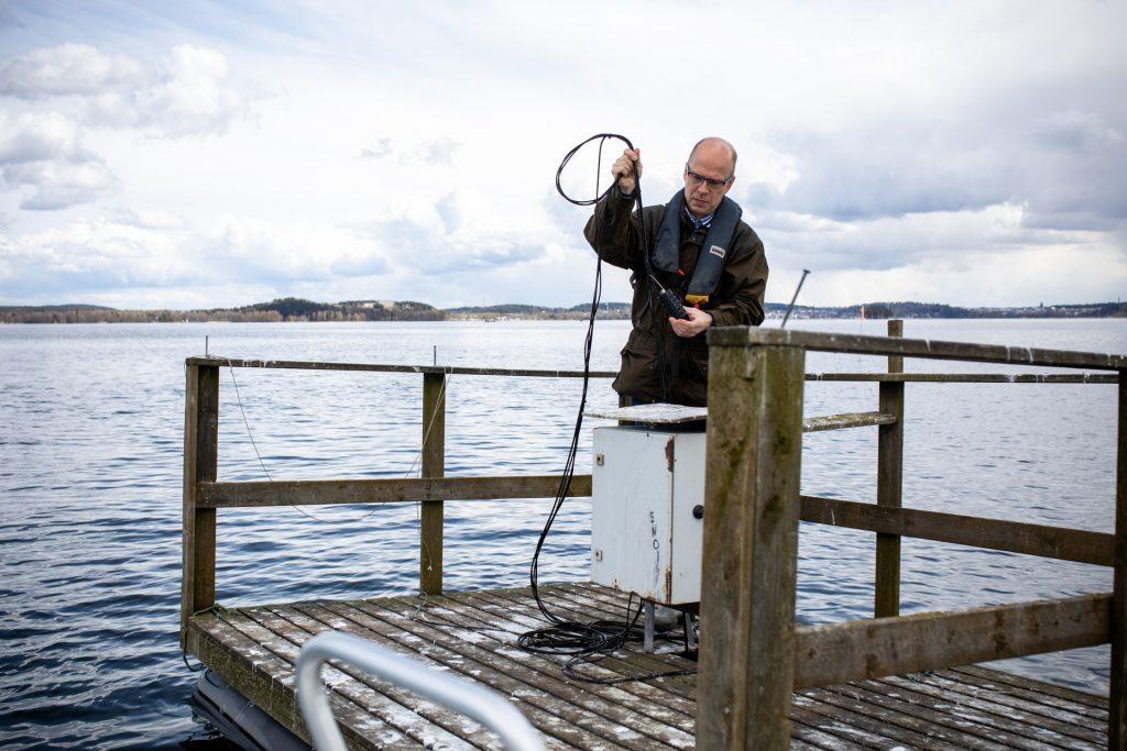 Mies tarkistaa laitetta Vesijärven mittauslautalla.