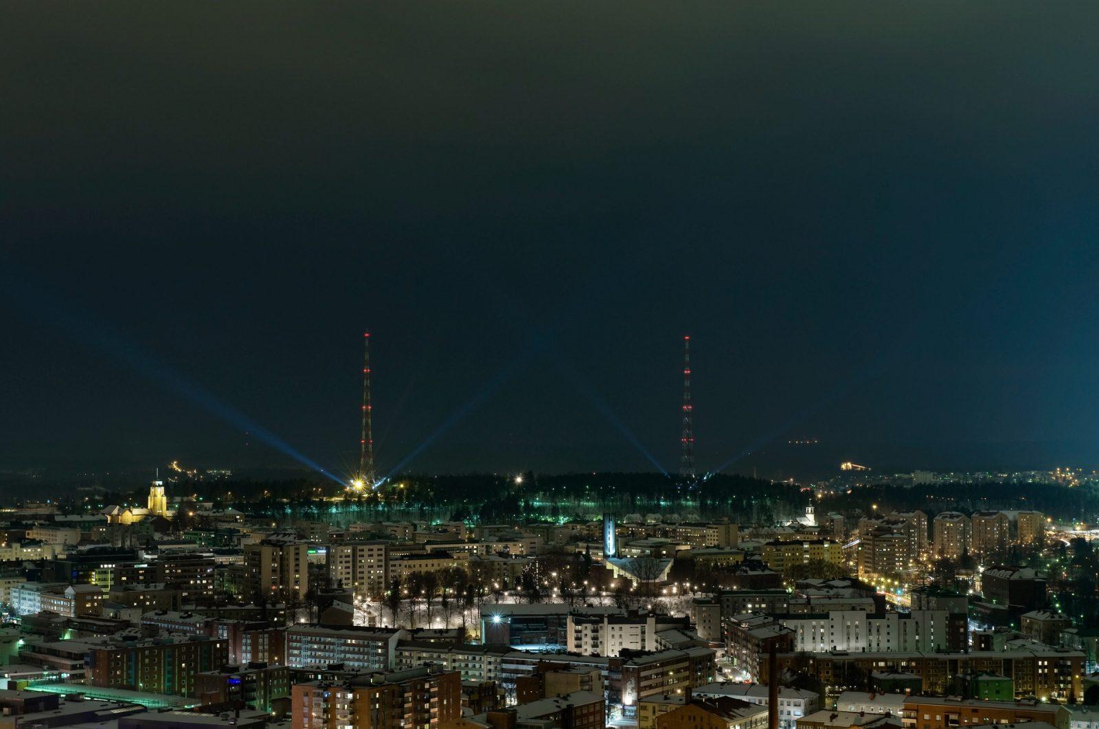 Kuvituskuva yöllisestä kaupungista, jossa kaupungin valaistus korostuu.
