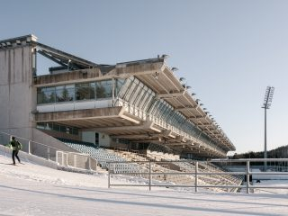 Hiihtäjä urheilukeskuksen stadionrakennuksen vieressä.