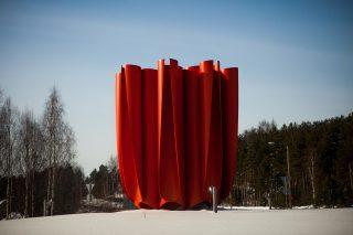 Punainen ja kookas taideteos sijaitsee liikenneympyrän keskellä.
