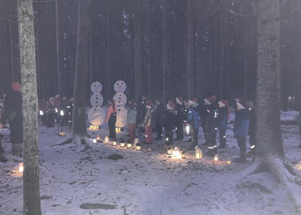 Koululaisten esityksessä rakentuu lumiukkopari metsään.