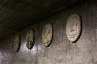 Teos koostuu alikulkutunnelin seinään kiinnitetyistä betonisista kasvoista.