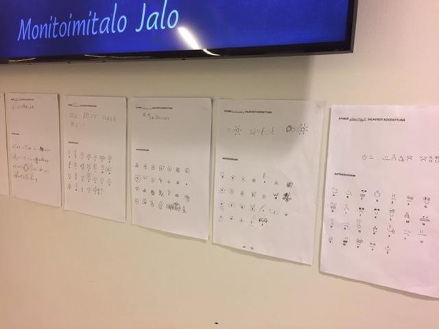 A4-arkkeja seinään kiinnitettynä, papereissa koodiviestejä