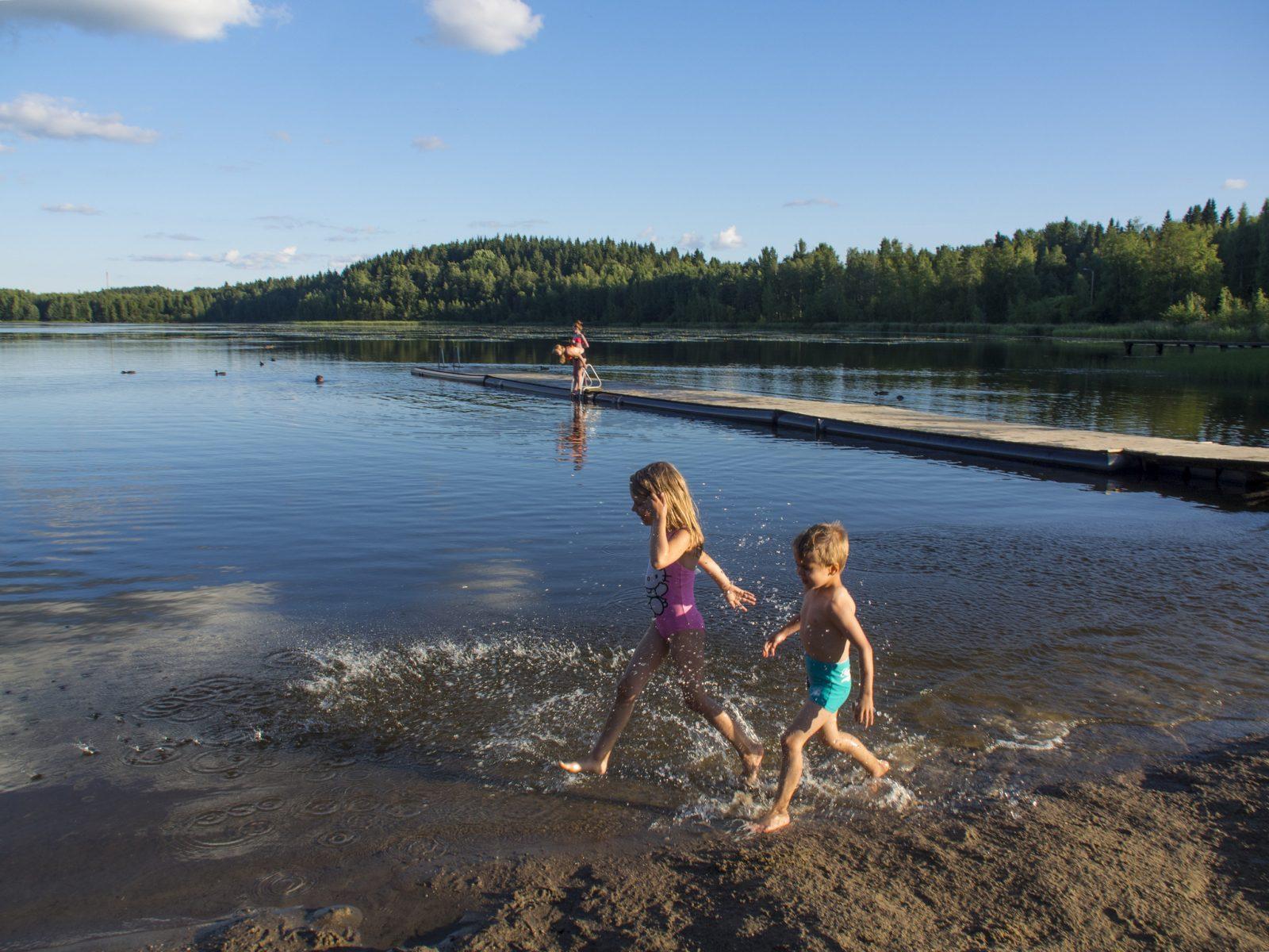 Kaksi lasta kahlaa uimarannalla aurinkoisena päivänä.