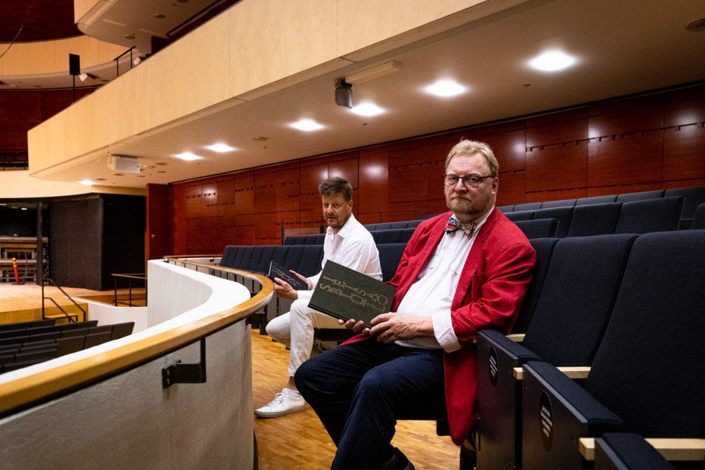 Kaksi miestä istuu konserttisalin penkeillä kirjat kädessä.