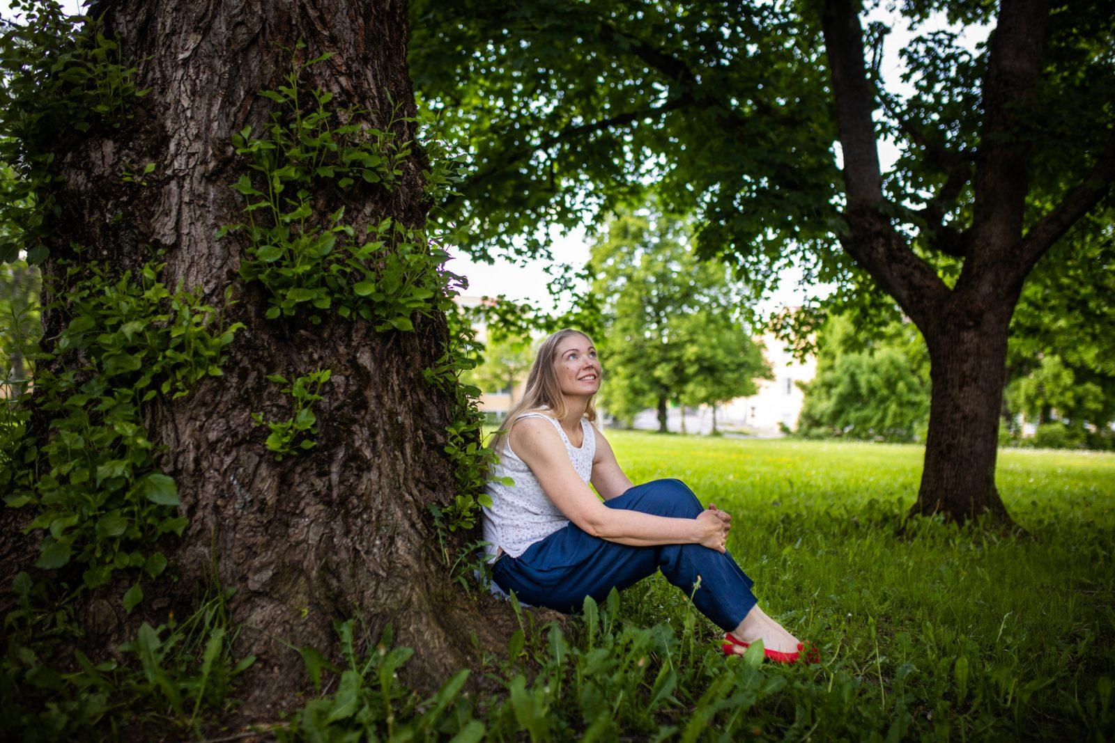 Henkilö istuu puun juurella nurmikolla.